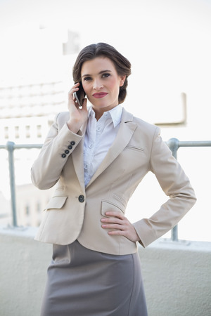 Stern stylish brown haired businesswoman making a phone call outdoors photo