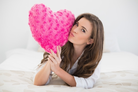 Beautiful casual brown haired woman in white pajamas kissing a heart shaped pillow in a bright bedroom photo