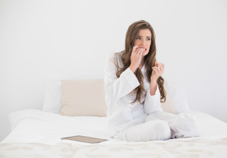 Worried casual brown haired woman in white pajamas sitting on her bed in bright bedroom photo