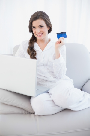 Pretty casual brown haired woman in white pajamas shopping online with her laptop in a bright living room photo
