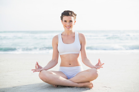 Smiling slim brown haired model in white sportswear meditating in lotus position on the beach photo