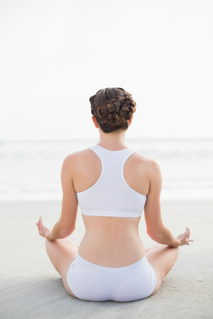 Attractive slim brown haired model in white sportswear meditating in lotus position on the beach photo