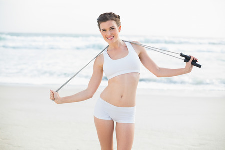 Pleased slim brown haired model in white sportswear holding a skipping rope on the beach photo