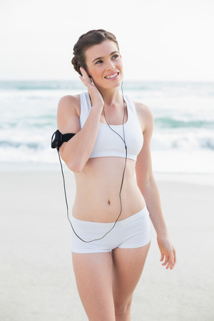 Thoughtful slim brown haired model in white sportswear listening to music on the beach photo