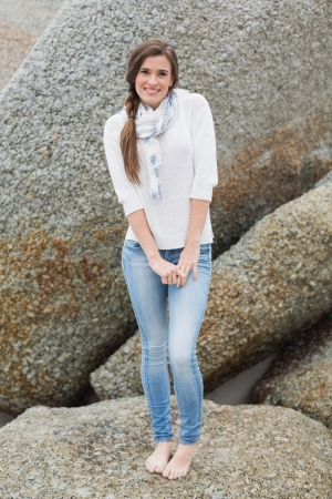 Cheerful young brown haired model posing looking at camera on a rock photo