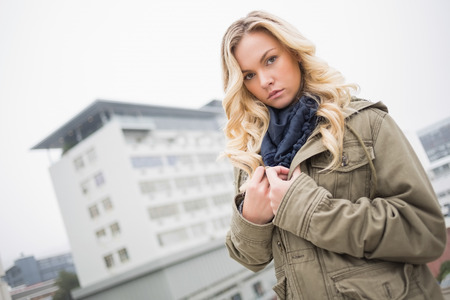 Serious attractive blonde posing outdoors on urban background photo