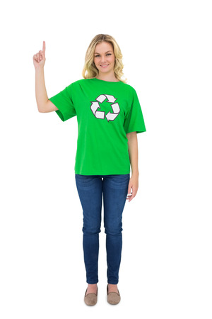 Smiling blonde environmental activist pointing up on white  photo