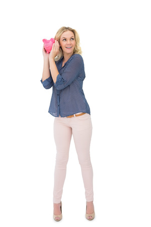Curious pretty blonde holding piggy bank on white background photo