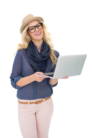 Happy trendy blonde holding laptop on white  photo