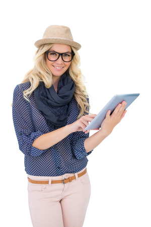 Happy trendy blonde holding tablet computer on white  photo