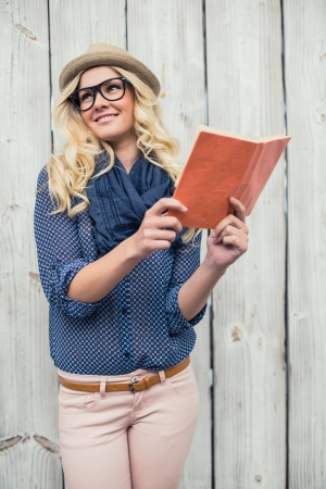 Cheerful fashionable blonde holding book outdoors on wooden  photo