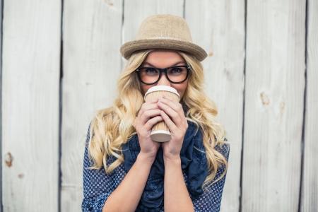 móda: S úsměvem módní blondýna pije kávu venku na dřevěné stěně