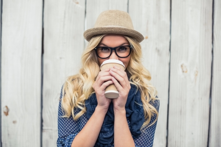 Smiling fashionable blonde drinking coffee outdoors on wooden wall photo