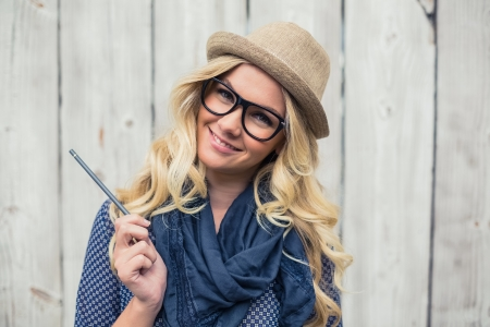 reading glasses: Smiling trendy blonde holding pencil on wooden