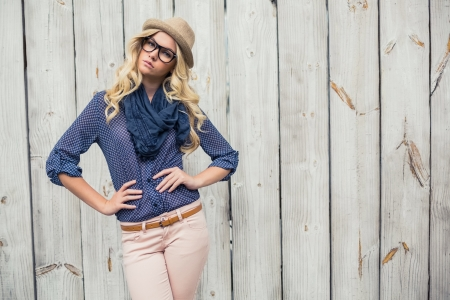 Day dreaming trendy blonde posing on wooden wall
