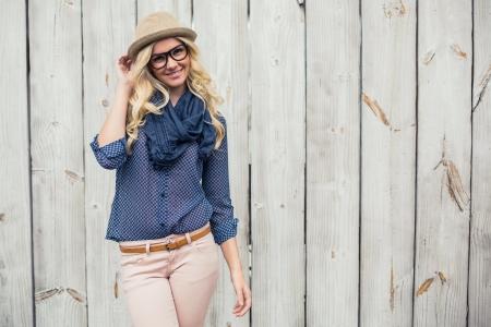 Smiling trendy Modell posiert auf Holzwand