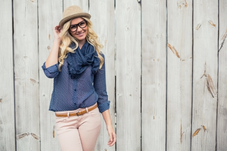 fashion: Sonriendo modelo de moda posando en la pared de madera Foto de archivo