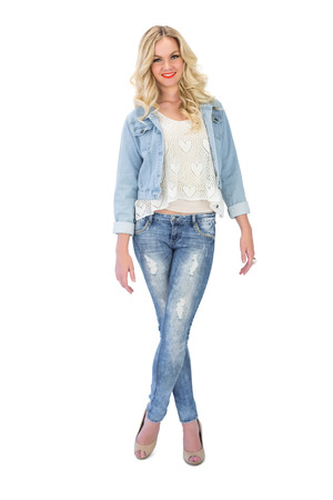Smiling casual blonde wearing denim clothes posing on white background photo