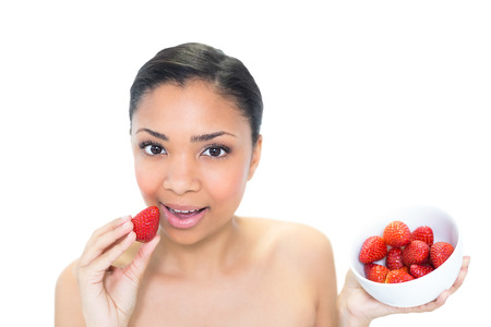 Relaxed young dark haired model eating strawberries on white  photo