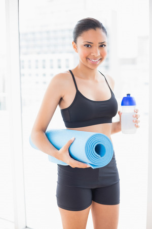 Cute dark haired model in sportswear carrying exercise mat and water in bright fitness studio photo