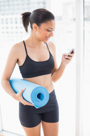 Pleased dark haired model in sportswear carrying an exercise mat and using a mobile phone in bright fitness studio photo