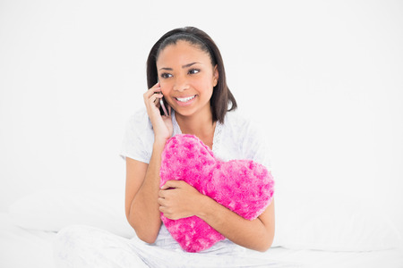 Pretty young dark haired model holding a pillow and making a phone call in bright bedroom photo
