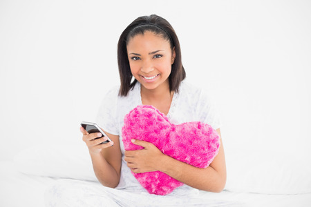 Delighted young dark haired model holding a pillow and a mobile phone in bright bedroom photo