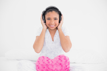 Cheerful young dark haired model listening to music with headphones in bright bedroom photo