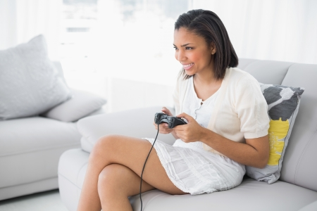 dark haired woman: Delighted young dark haired woman in white clothes playing video games in a living room Stock Photo