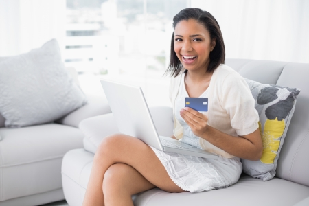 Laughing young dark haired woman in white clothes shopping online with a laptop in a living room photo