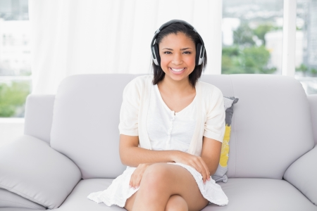 Smiling young dark haired woman in white clothes listening to music in a living room photo
