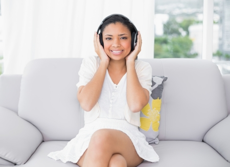 Pleased young dark haired woman in white clothes listening to music in a living room photo