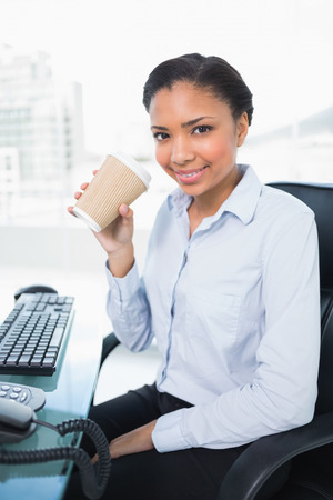 Amused young dark haired businesswoman drinking coffee in bright office Stock Photo - 25452429