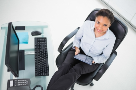 Stylish young dark haired businesswoman using a tablet pc in bright office photo