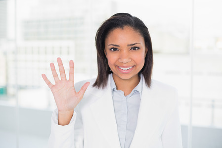 Pretty young dark haired businesswoman waving her hand in bright office Stock Photo - 25452435