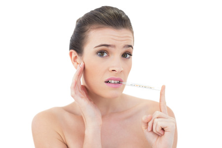 Anxious natural brown haired model using a thermometer on white  Stock Photo - 25388146