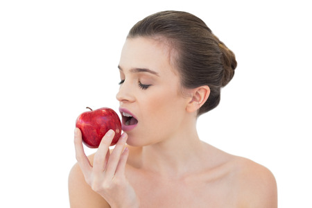 Relaxed natural brown haired model biting an apple on white background photo