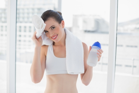 Tired fit brown haired model in sportswear wiping her brow with a towel in bright fitness studio photo