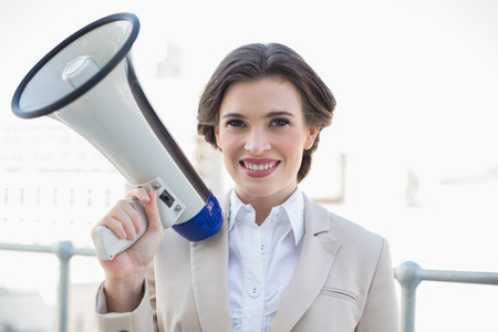 Pleased stylish brown haired businesswoman holding a megaphone outdoors photo