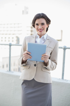 Smiling stylish brown haired businesswoman holding a tablet pc outdoors photo