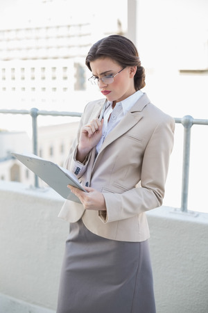 Troubled stylish brown haired businesswoman looking at a report outdoors photo