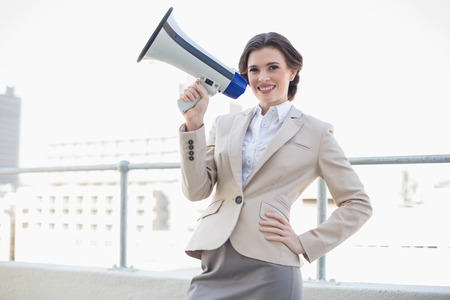 Charming stylish brown haired businesswoman holding a megaphone outdoors photo