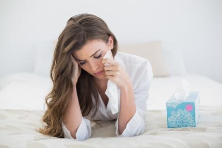 femme triste: D�prim� occasionnel femme brune � poil dans des pyjamas blancs pleurer sur son lit dans une chambre lumineuse