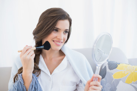 powder room: Cheerful casual brown haired woman in white pajamas applying powder on her face in a bright living room