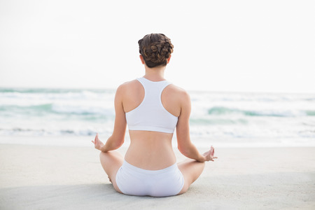 Gorgeous slim brown haired model in white sportswear meditating in lotus position on the beach photo