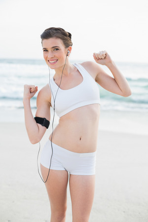 Motivated slim brown haired model in white sportswear listening to music on the beach photo