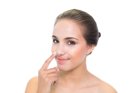 long nose: Lovely young brunette woman touching her nose on white  Stock Photo