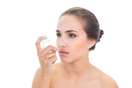 Upset young brunette woman holding an inhaler on white  photo
