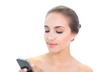 Content young brunette woman holding a smartphone on white background photo