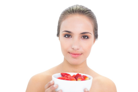 Smiling young brunette woman holding a bowl of strawberries on white  photo